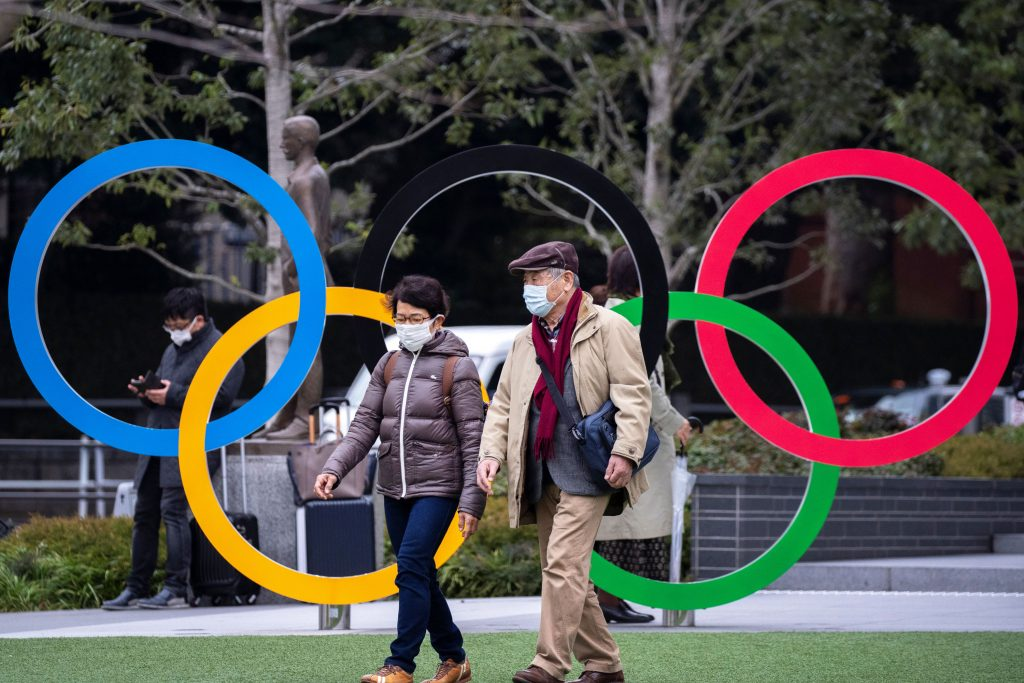 People wearing protective face masks, following an outbreak of the coronavirus, are seen next to the Olympic rings in front of the Japan Olympic Museum in Tokyo, Japan, February 26, 2020.