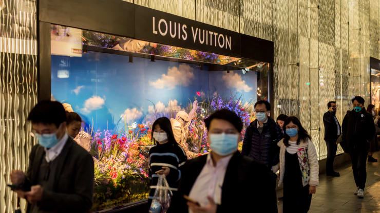 Pedestrians wearing protective masks walk past an LVMH Moet Hennessy Louis Vuitton SE in the Central district of Hong Kong, China, on Tuesday, Feb. 11, 2020.
