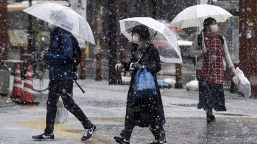 Snow falls as people wearing face masks walk through the Asakusa district on March 29, 2020 in Tokyo, Japan.