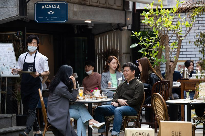 People sit at a cafe in the Garosu-gil neighborhood of the Gangnam district of Seoul, April 18.Photographer: SeongJoon Cho