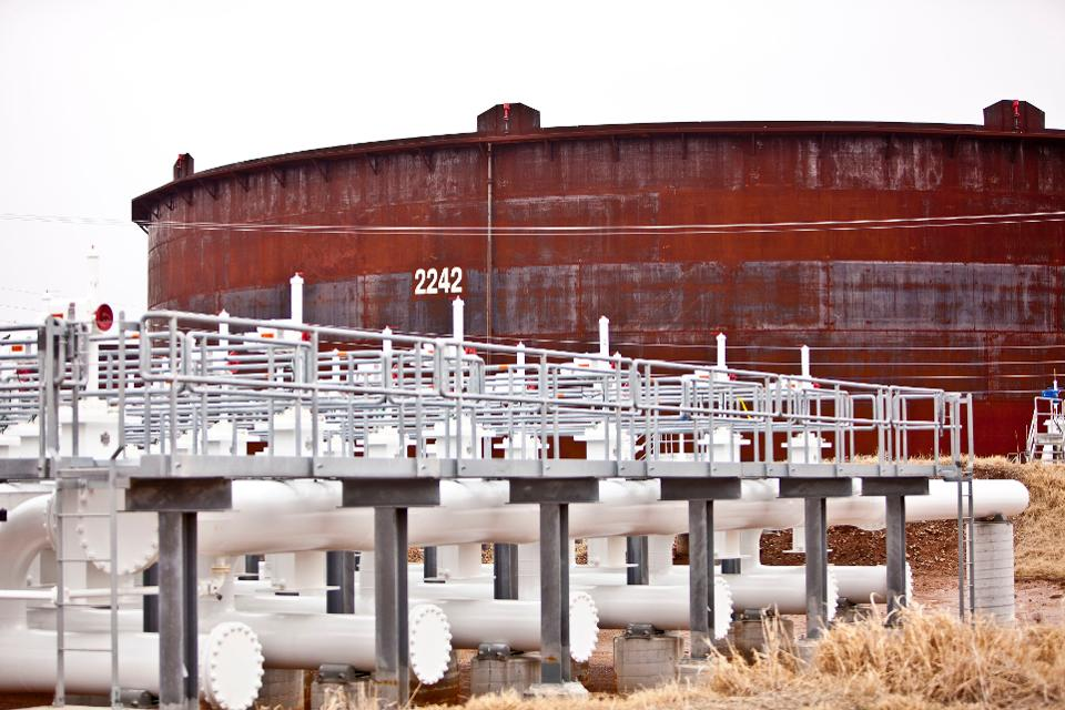Control manifolds sit near an oil storage tank at the Enbridge Inc. Cushing Terminal in Cushing, Oklahoma, U.S. (Photo: Shane Bevel/Bloomberg) BLOOMBERG NEWS