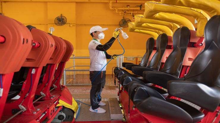 A worker wearing a protective mask sprays a nano-photocatalytic coat on a roller coaster train during a media tour at Ocean Park, temporarily closed due to the coronavirus, in Hong Kong, China, on Friday, May 8, 2020. The theme park has been temporarily closed since Jan. 26 due to the pandemic.