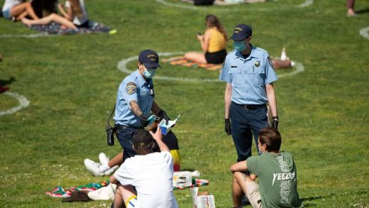 San Francisco police officer cadets distribute face masks to people at Dolores Park in San Francisco, California on May 22, 2020 amid the novel coronavirus pandemic. JOSH EDELSON/AFP via Getty Images