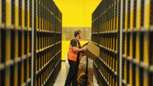 A worker assembles a box for delivery at the Amazon fulfillment center in Baltimore, Maryland