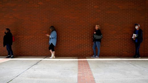 People wait in line to file for unemployment in Fayetteville, Arkansas.