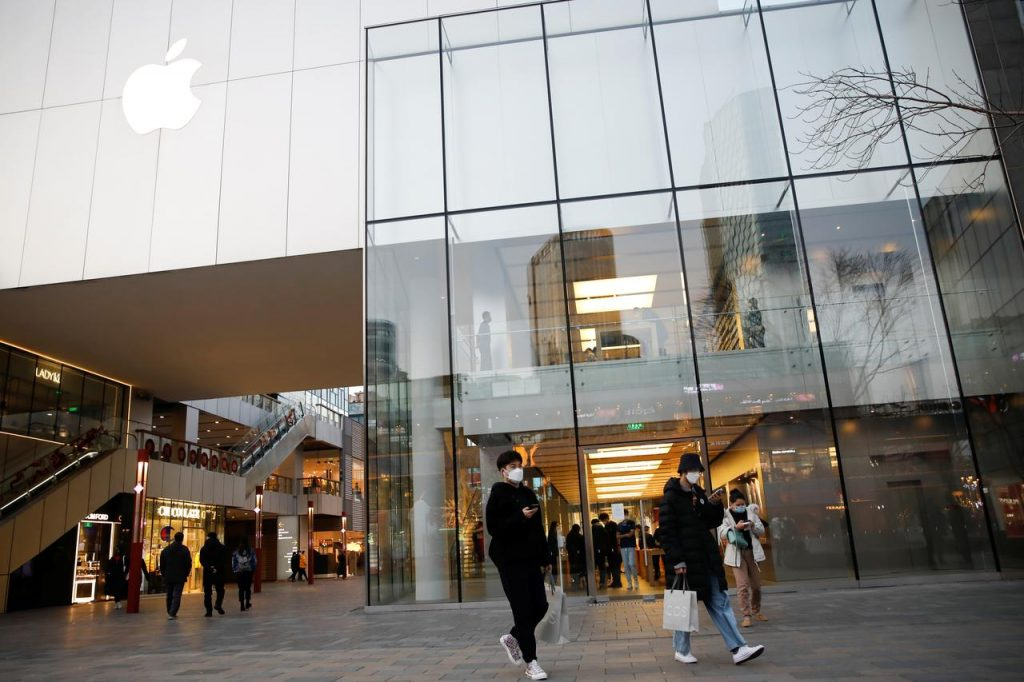 People wearing face masks walk past an Apple store in Beijing on March 17, 2020 in Beijing, China.