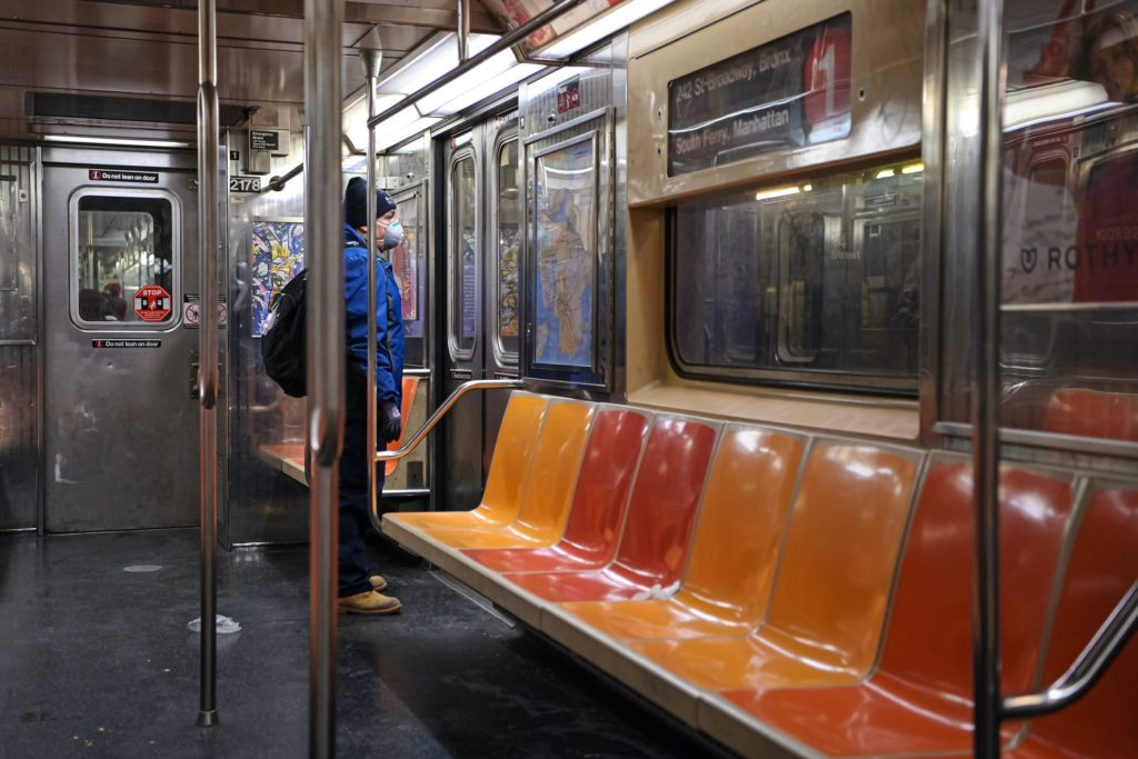 A woman wearing a face mask looks out of the window of a NYC subway train amid the coronavirus outbreak.