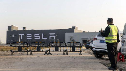 Workers walk outside the Tesla Inc. Gigafactory in Shanghai, China