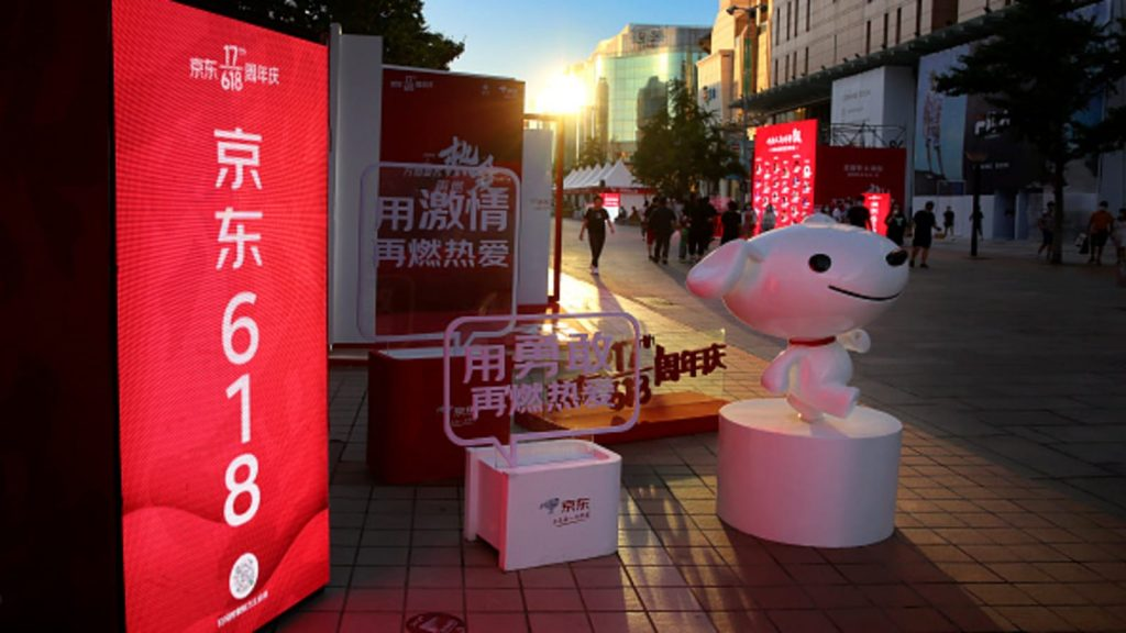 People walk by JD.com advertisements of the 618 Shopping Festival at Wangfujing Street on June 14, 2020 in Beijing, China
