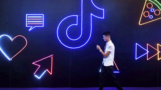A man holding a phone walks past a sign of Chinese company ByteDance's app TikTok, known locally as Douyin, at the International Artificial Products Expo in Hangzhou, Zhejiang province, China October 18, 2019. Reuters