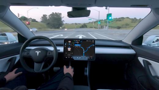 A Tesla employee demonstrates Autopilot