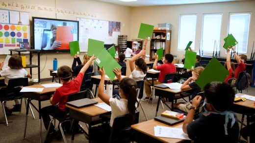 Students wearing protective masks raise their hands in a classroom as a teacher gives a lesson remotely at a public charter school in Provo, Utah, U.S., on Thursday, Aug. 20, 2020.