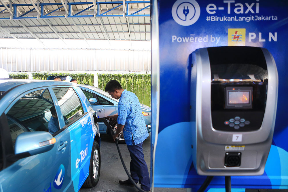 A Blue Bird driver operates the BYD electric car charger during the unveiling of the first electric taxi in Indonesia in Jakarta. Blue Bird Holding Group officially operates 25 BYD electric cars for Blue Bird and four Tesla Model X vehicles used by Silver Bird.(The Jakarta Post/Seto Wardhana)