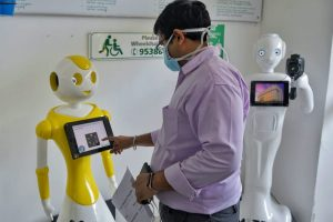 "Hospital staff at Fortis Hospital in Bangalore with ""Mitra,"" a robot helping to screen coronavirus patients."