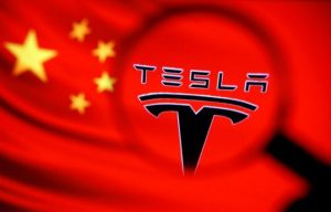 Chinese flag and Tesla logo is seen through a magnifier in this illustration taken January 7, 2021. REUTERS/Dado Ruvic/Illustration