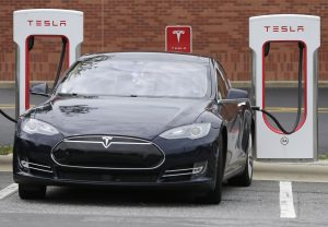 FILE- In this June 24, 2017, file photo, a Telsa car recharges at a Tesla charging station at Cochran Commons shopping center in Charlotte, N.C. Tesla Inc. reports earnings Wednesday, Feb. 7, 2018. (AP Photo/Chuck Burton)
