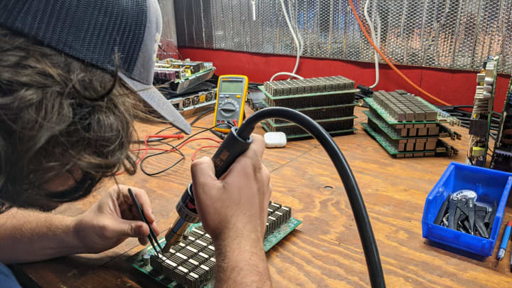 Lead technician Nick Sears repairs hardware at the SCATE Ventures Inc. mining farm in Dallesport, Washington.
