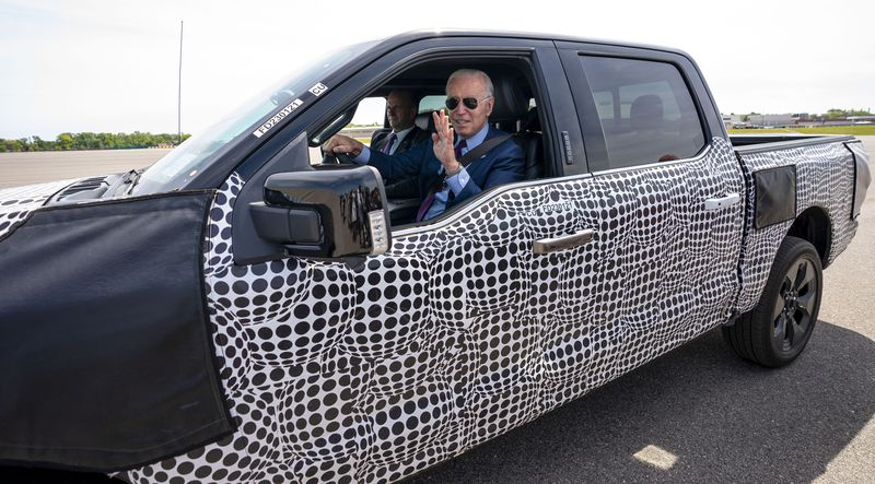 President Joe Biden stops to talk to the media as he drives a Ford F-150 Lightning truck at Ford Dearborn Development Center, Tuesday, May 18, 2021, in Dearborn, Michigan. (AP Photo/Evan Vucci)