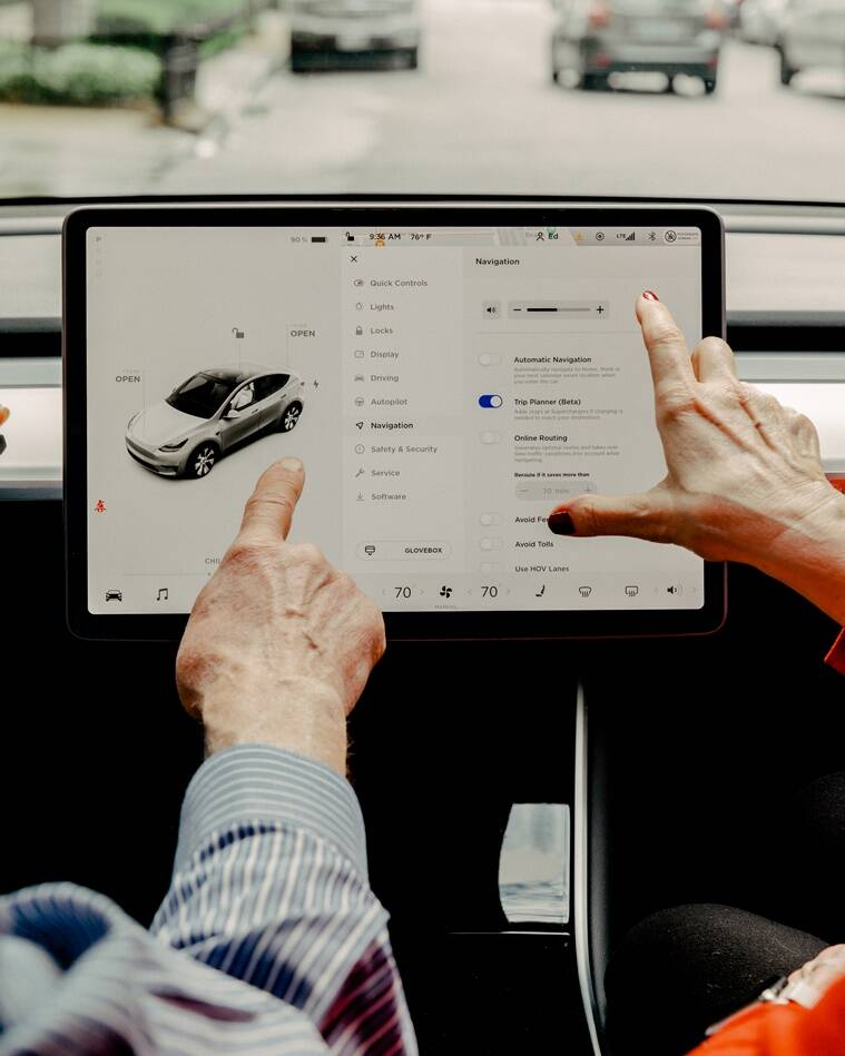 A couple demonstrates some of the options and capabilities that are accessible via the touch-screen of their Tesla automobile in Chicago, June 4, 2021. (File/The New York Times)