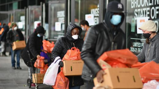 People pick up food the Food Bank at the New York City mobile food pantry on the Barclays Center plaza on April 24, 2020 in the Brooklyn, New York.