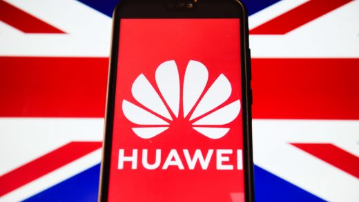 Huawei logo is seen on a smartphone in front of a laptop displaying the U.K. flag.