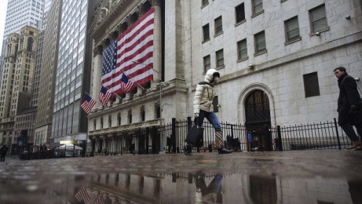 A man wears a protective mask as he walks on Wall Street during the coronavirus outbreak in New York City, New York, U.S., March 13, 2020.