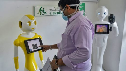 """Hospital staff at Fortis Hospital in Bangalore with """"Mitra,"""" a robot helping to screen coronavirus patients."""