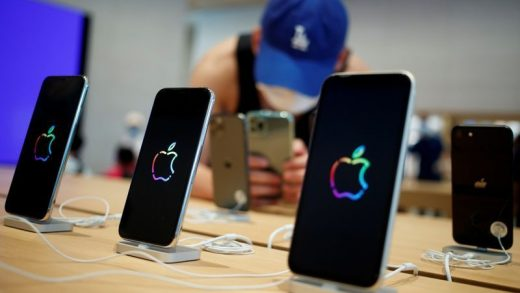 FILE PHOTO: A man takes pictures of iPhones in the new Apple flagship store on its opening day following an outbreak of the coronavirus disease (COVID-19) in Sanlitun in Beijing, China, July 17, 2020. REUTERS/Thomas Peter