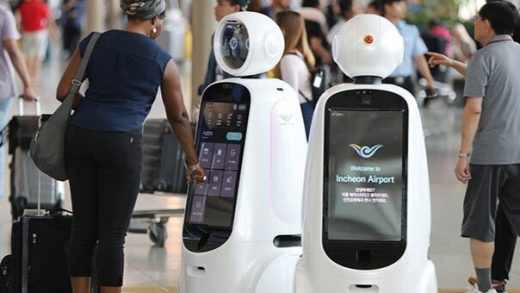 Travelers wearing protective masks stand next to a robot at Incheon International Airport in Incheon, South Korea. Photographer: SeongJoon Cho/Bloomberg