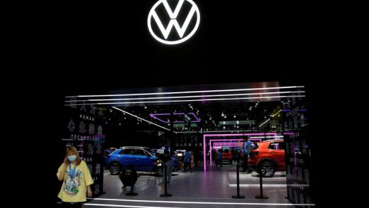 FILE PHOTO: A woman wearing a face mask following the coronavirus disease (COVID-19) outbreak stands under a sign of Volkswagen at the Beijing International Automotive Exhibition, or Auto China show, in Beijing, China, September 27, 2020. REUTERS/Tingshu Wang