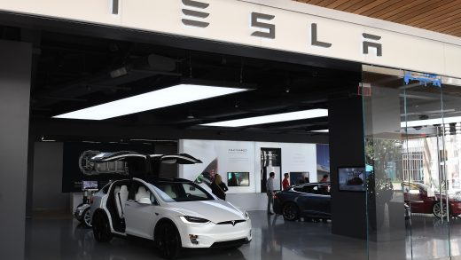 People stand in a Tesla showroom at a shopping mall in Los Angeles on April 25, 2019. - Electric carmaker Tesla on April 24 announced a heavy loss in the first quarter of 2019 as car deliveries sputtered overseas and a US tax credit that made its prices more attractive was reduced. The California-based company reported a loss of $702 million in the first three months of this year after two consecutive quarters of profit. (Photo by Mark RALSTON / AFP) (Photo credit should read MARK RALSTON/AFP/Getty Images)